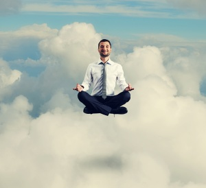 man in formal wear meditating in the sky